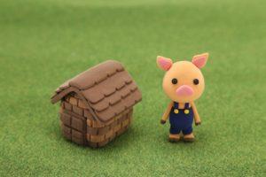 芝生の上の子豚とレンガの家
